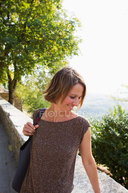 Portrait of Woman looking over wall — Stock Photo