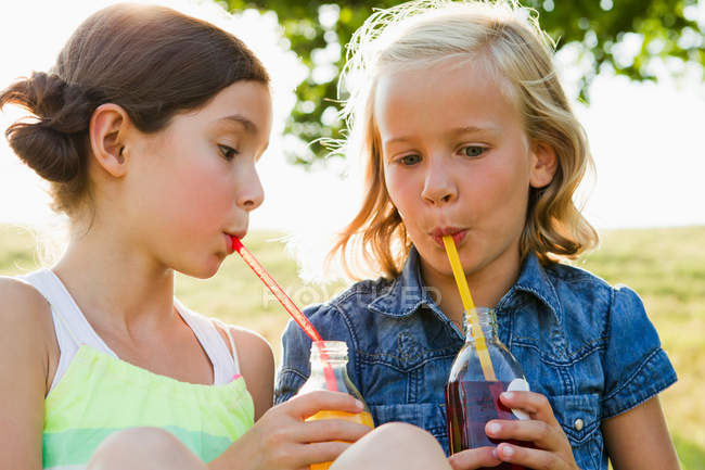 Laughing girls drinking juice outdoors — Foto stock
