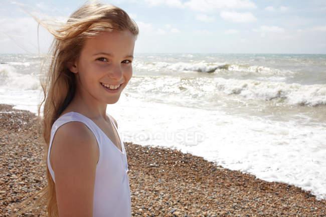 Menina na praia à beira-mar, sorrindo para a câmera — Fotografia de Stock