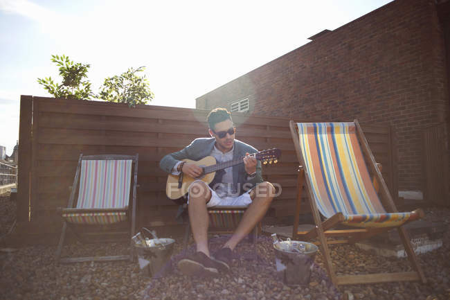 Mid adult man playing guitar on deckchair at rooftop party — Stock Photo