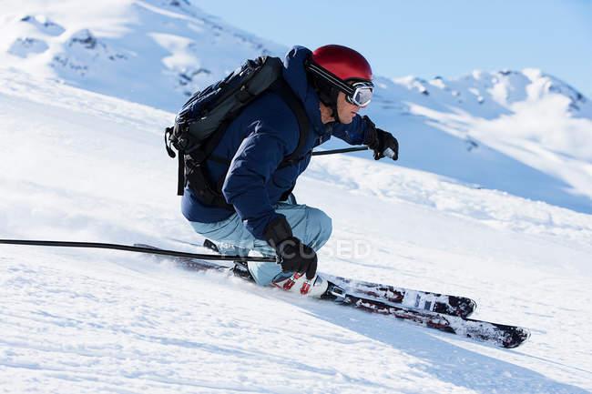 Мужчины лыжник, ускорение вниз горы — стоковое фото