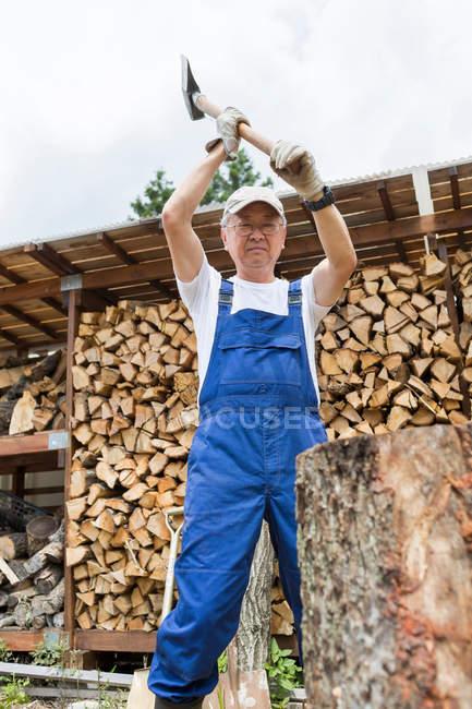 Homme coupant du bois de chauffage à l'extérieur — Photo de stock
