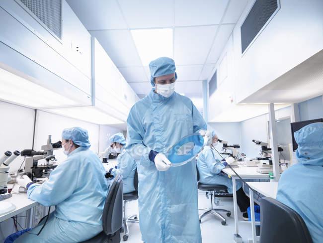 Працівник електроніки в чистій кімнаті тримає кремнієвої пластини — стокове фото