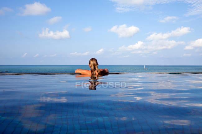 Back view of Woman relaxing in infinity pool — Stock Photo