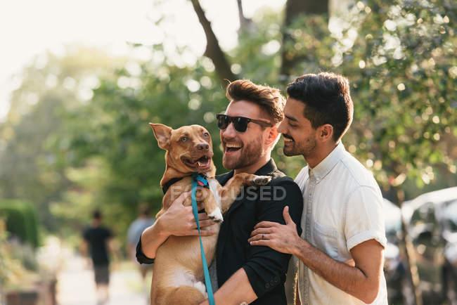 Giovane coppia maschile che trasporta cane sul marciapiede suburbano — Foto stock