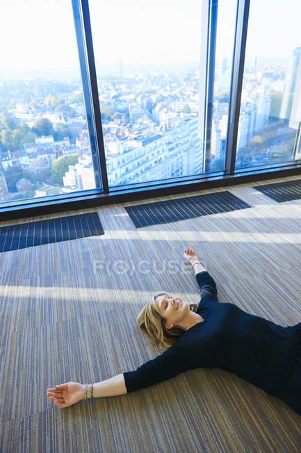 Reife Frau praktizieren Yoga im Raum — Stockfoto