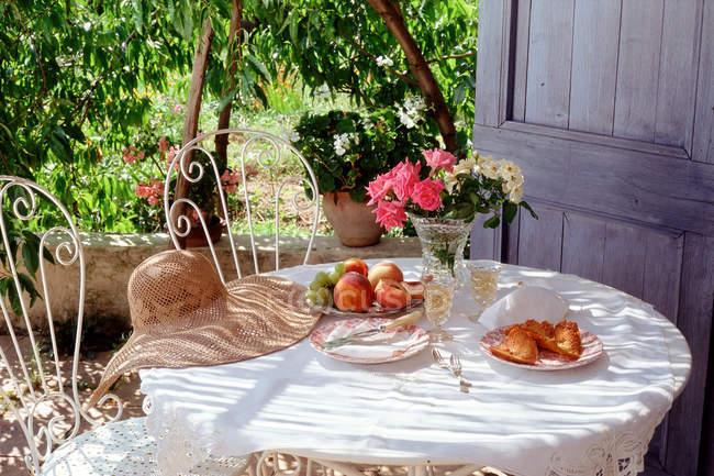 Mesa de jardim servido com chapéu com cadeiras ornamentadas — Fotografia de Stock