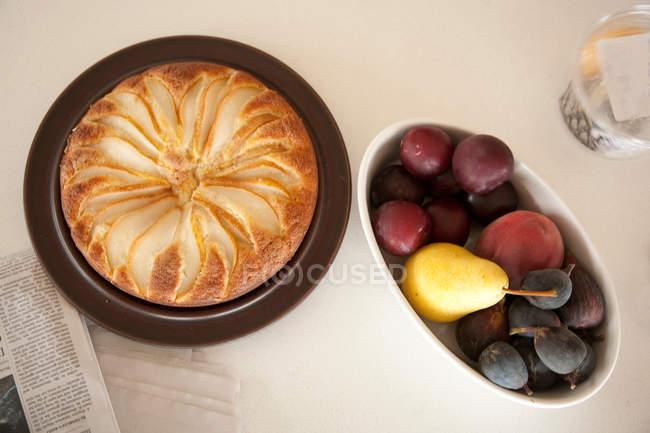 Piatto di frutta e budino di pane sul tavolo — Foto stock