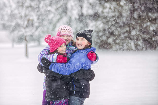 Friends embracing in snowfall — Stock Photo