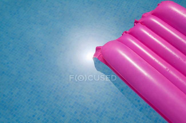 Colchão inflável rosa na piscina — Fotografia de Stock