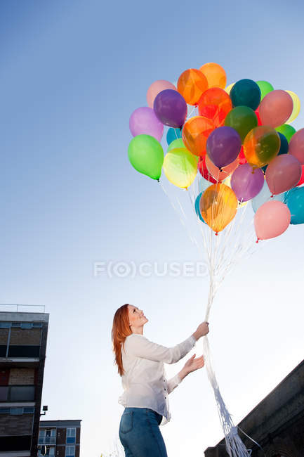 Young woman outdoors with balloons — Stock Photo