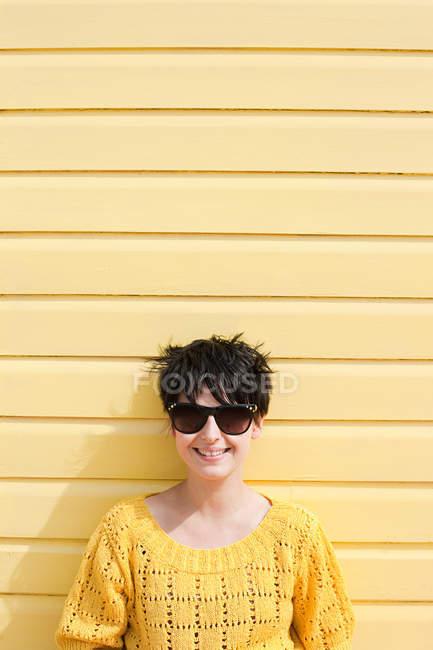 Jovem mulher e parede amarela — Fotografia de Stock