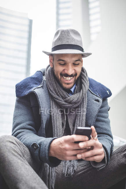 Smiling businessman sitting on stairway and using smartphone — Stock Photo