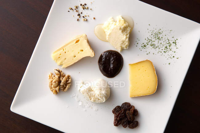 Cheeses with nuts and sauce on plate — Stock Photo