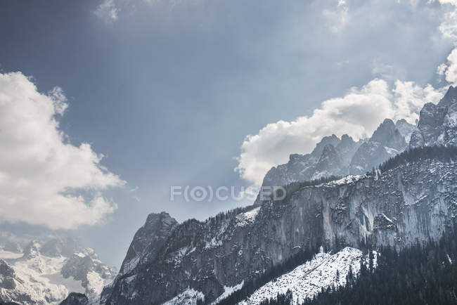 Snow covered mountains under blue cloudy sky — Stock Photo
