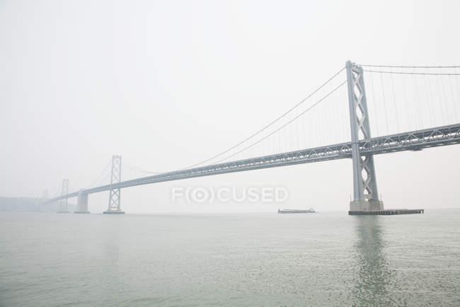 Vista a distanza del Bay Bridge con tempo nebbioso, San Francisco, USA — Foto stock