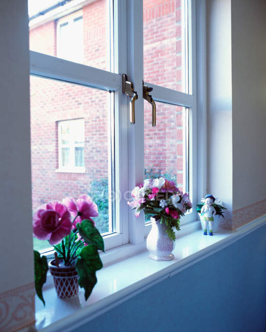 Close up of windowsill with flowers in ceramic vases — Stock Photo