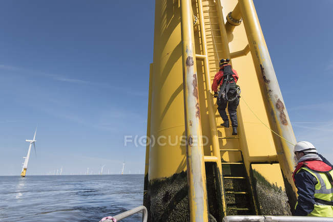 Engineers climbing wind turbine ladder from boat at offshore windfarm — Stock Photo