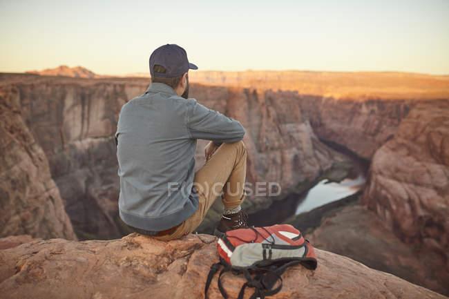 Man sitting on rock, looking at view, Page, Arizona, USA — Stock Photo