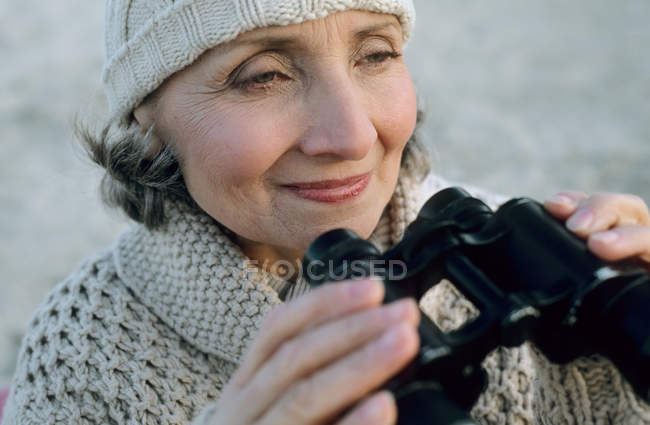 Senior woman using binoculars — Stock Photo