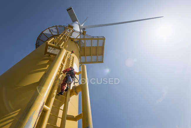 Engineers climbing wind turbine from boat at offshore windfarm, low angle view — Stock Photo