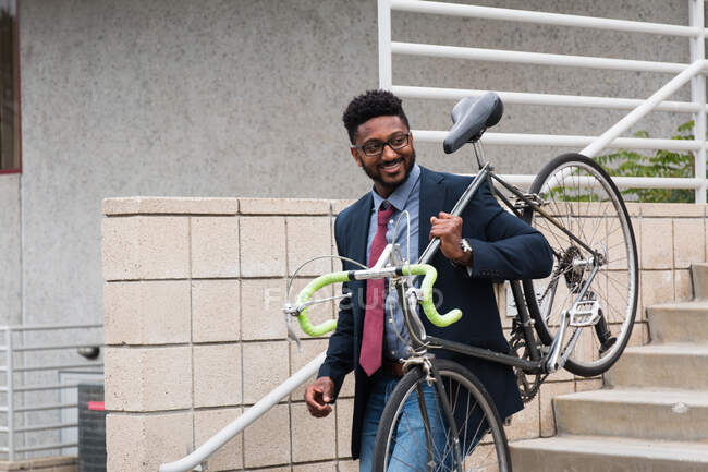 Young man carrying bicycle down steps — Stock Photo
