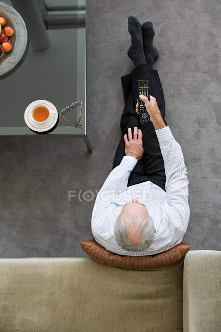 Overhead view of Senior man watching television — Stock Photo