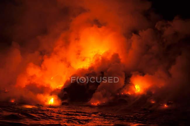 Fumar nuvens de fluxo de lava, impactando o mar à noite, o vulcão Kilauea, Havaí — Fotografia de Stock