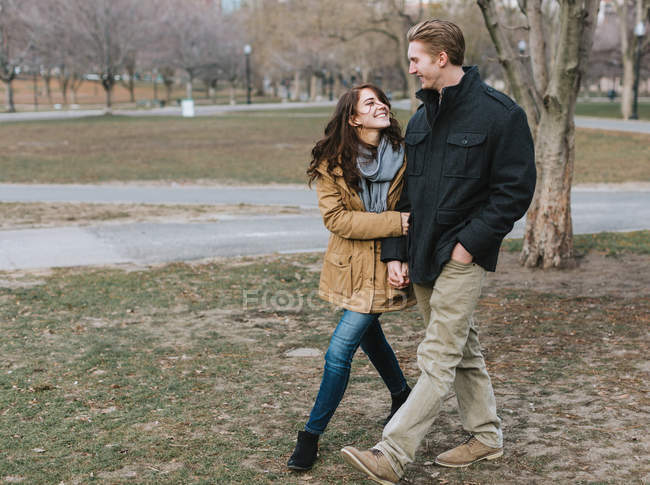 Young couple walking through park, arm in arm, smiling — Stock Photo