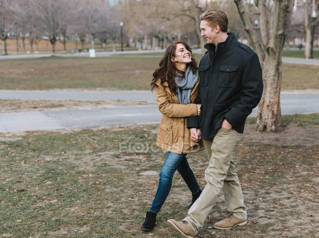 Pareja joven caminando por el parque, brazo en brazo, sonriendo - foto de stock