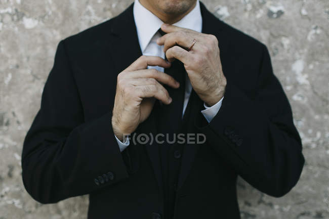 Cropped image of groom standing near wall — Stock Photo