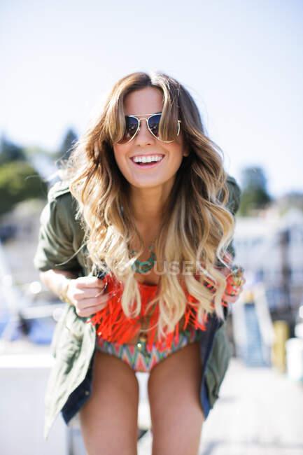 Ritratto di felice giovane donna appoggiata in avanti sulla spiaggia — Foto stock