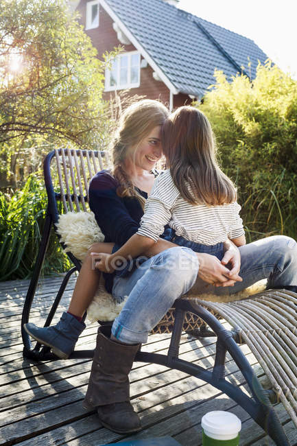 Daughter sitting on mother's lap on lounge chair on wooden decking — Stock Photo