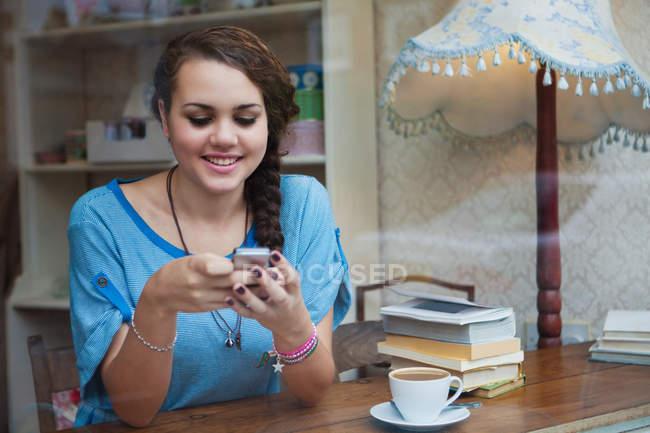 Giovane donna in caffè utilizzando il cellulare — Foto stock