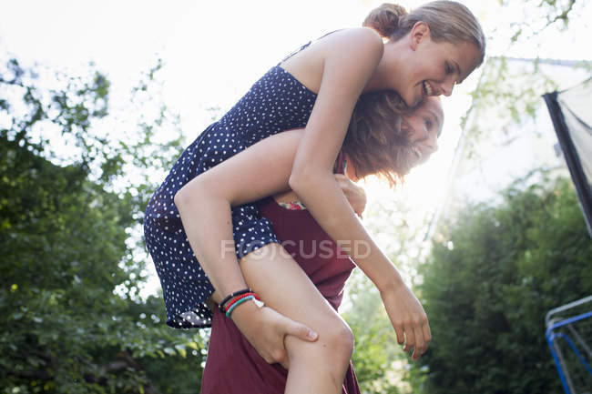 Teenage girl giving best friend a piggy back in park — Stock Photo