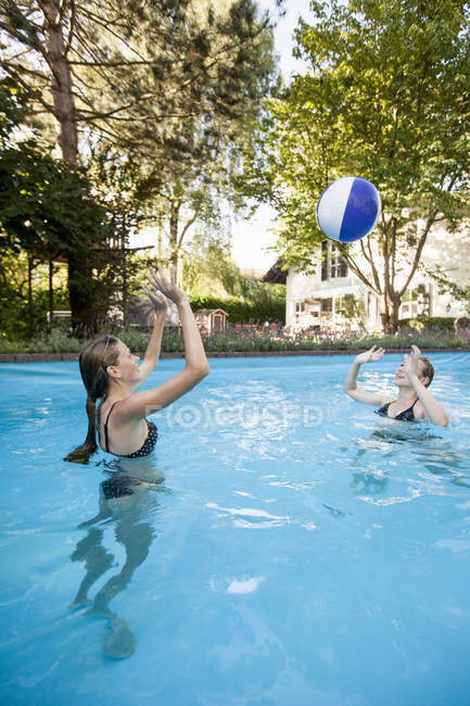 Two teenage girls playing with beach ball in swimming pool — Stock Photo