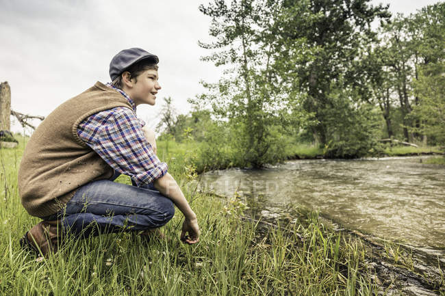 Side view of teen boy wearing flat cap crouching on riverbank looking away smiling — Stock Photo