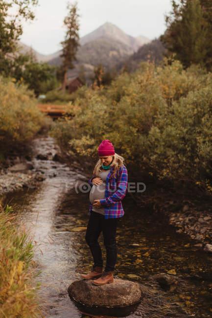 Mujer embarazada, de pie sobre roca en arroyo, sosteniendo el estómago, Rey Mineral, Parque Nacional Sequoia, California, EE.UU. - foto de stock