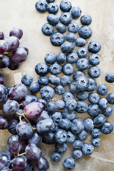 Top view of ripe grapes and blueberries on table — Stock Photo