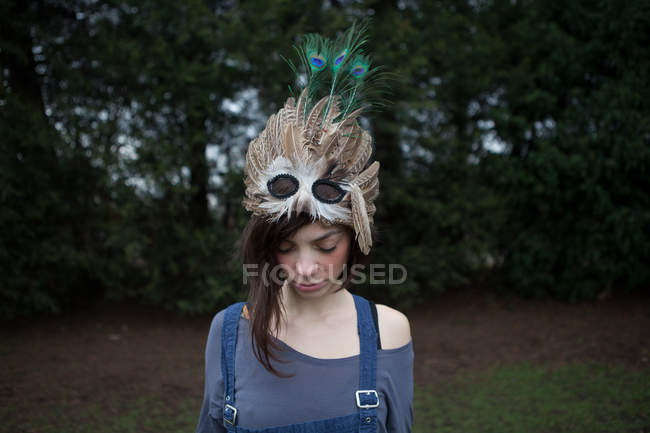 Young woman with feathered mask on her head — Stock Photo