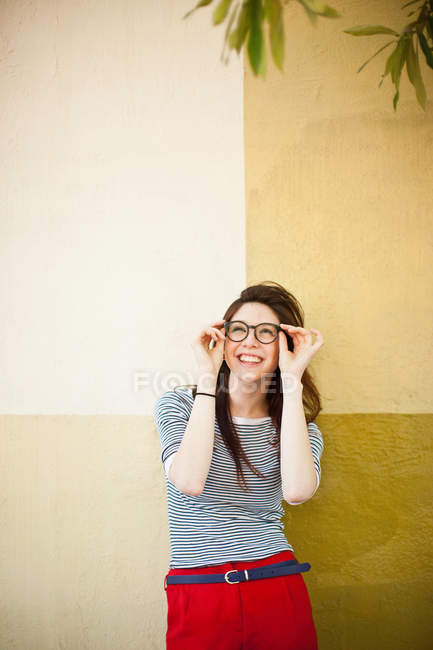 Portrait of young woman in front of color divided wall — Stock Photo