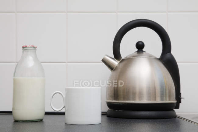 Kettle with cup and milk bottle — Stock Photo