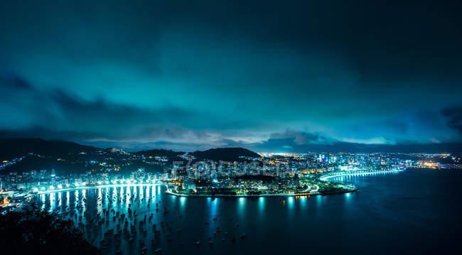 Vista de ángulo alto de la bahía de Botafogo, iluminada por la noche, Rio de Janeiro, Brasil - foto de stock