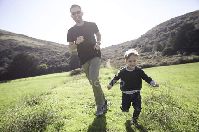 Батько і син біжить на відкритому повітрі — стокове фото