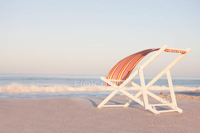 Deckchair on beach with striped textile flapping on wind — Stock Photo