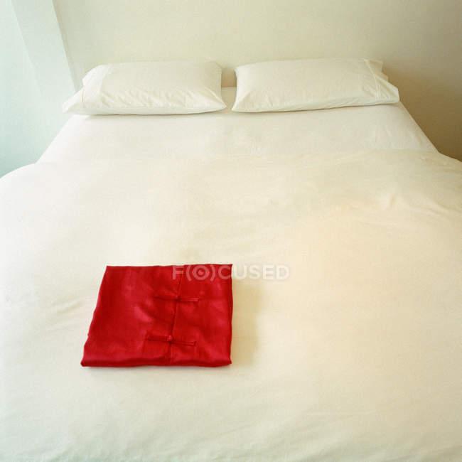 Pijama rojo doblado en cama blanca - foto de stock
