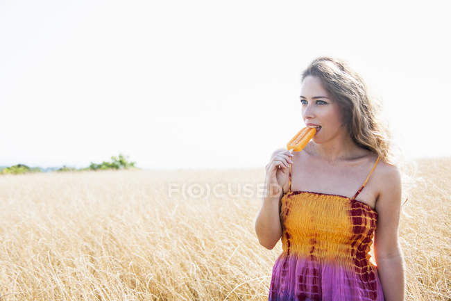 Ritratto di donna adulta, vestita da hippy, sul campo, che mangia ghiacciolo — Foto stock