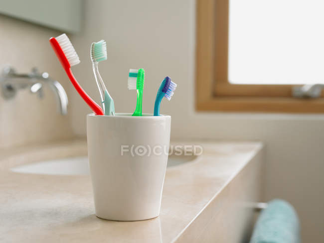 Colorful toothbrushes in cup at washbasin — Stock Photo