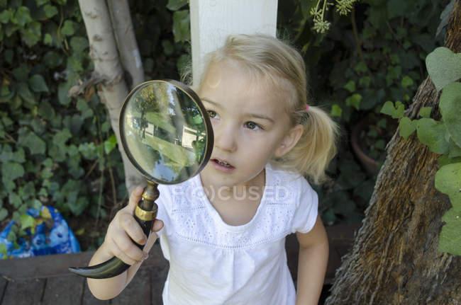 Chica joven mirando a través de lupa - foto de stock