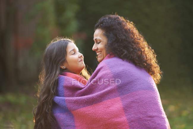 Мати і дочка загорнутий в ковдру в саду — стокове фото
